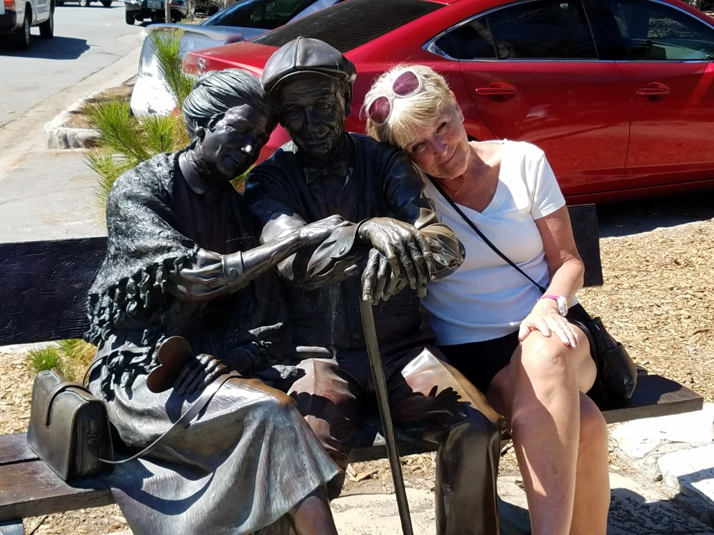 Founder, Carol Bokan, relaxs wit h a statue of a senior couple
